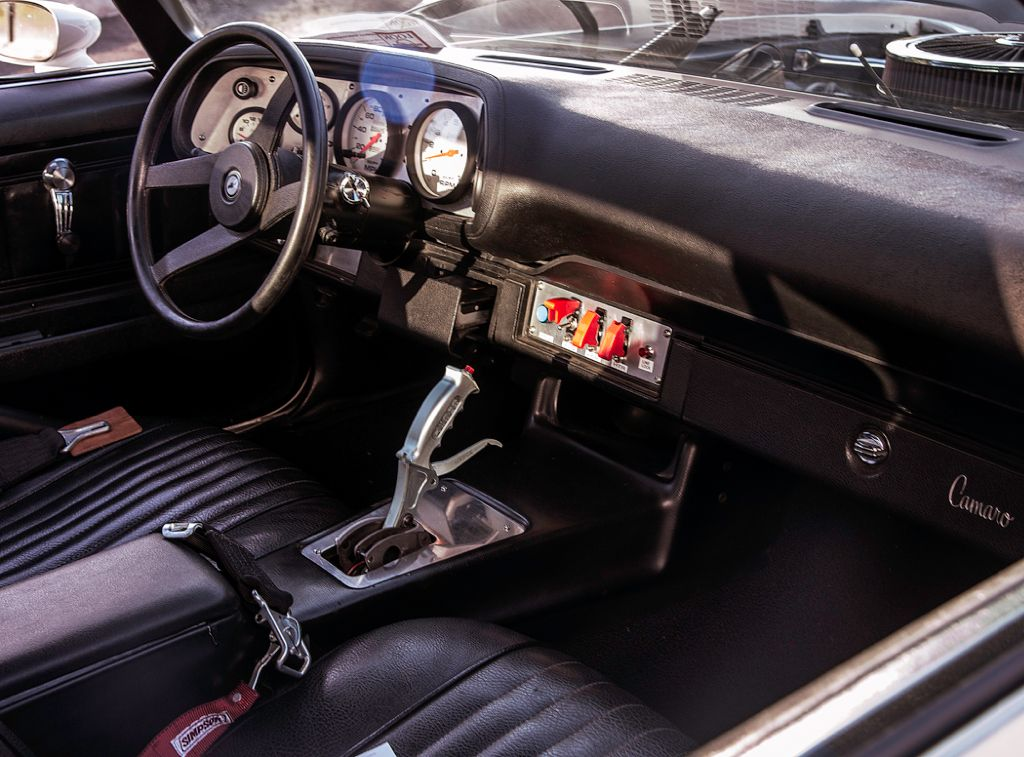 Auto Meter Phantom gauges, a Simpson 5-point harness, and a Hurst Quarter Stick shifter accent the interior.
