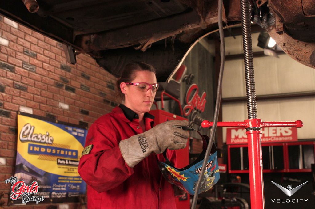All Girls Garage member Bogi examines the 'Cuda's undercarriage. After cleaning out the dirt and rust, the car's suspension, brakes, fuel tank, and more will be replaced with new parts from Classic Industries.