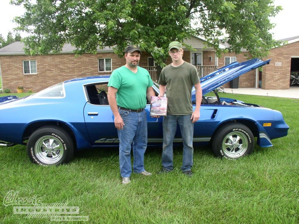 Eric and Jacob Nix standing in front of their Camaro, well-used Classic Industries catalog in hand.